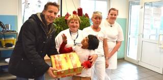 André Dölken, Betriebsleiter der Servico FM, übergibt neben der Spende in Höhe von 1.000 Euro auch einen Karton mit Süßigkeiten an das Küchenteam vom Friedensdorf International.