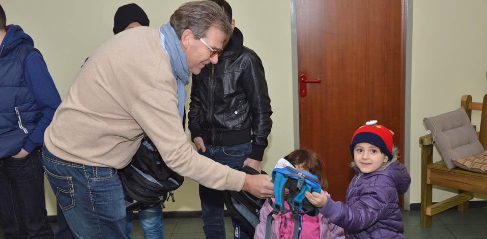 Franz Wisniewski von der Servico AG übergibt Kindergartenrucksack für Flüchtlingskind in Dinslaken