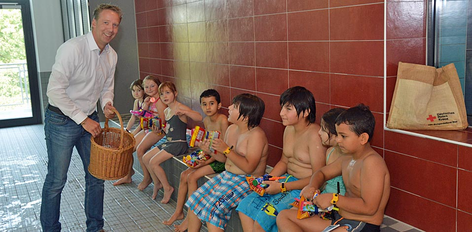 André Dölken von der Servico FM überreicht den Kindern des Schwimmkurses ein kleines Präsent.